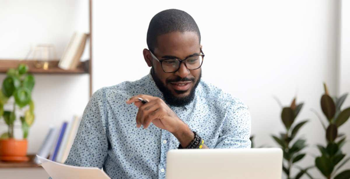 man holding papers and looking happily at laptop screen