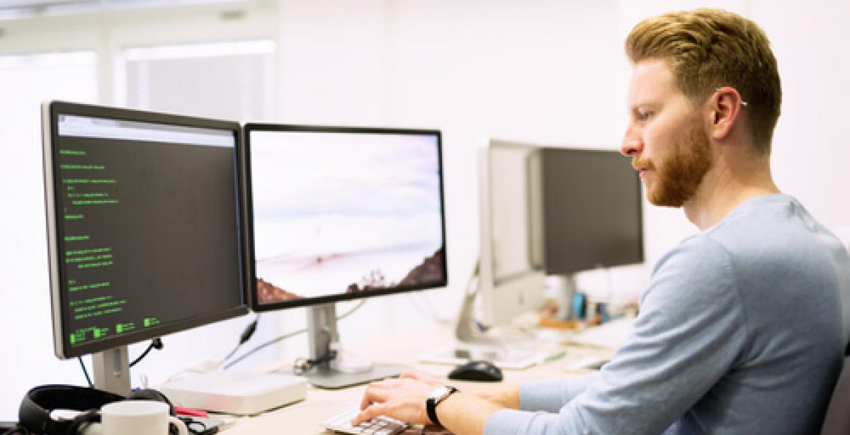 person doing advanced computer programming on two screens