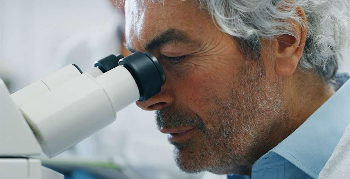 forensic criminologist using microscope
